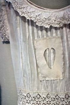 Cut-out heart stitched over muslin/lace dress.