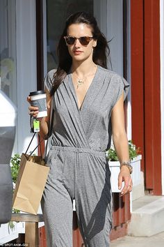 Gorgeous in grey: The 34-year-old supermodel highlighted her fantastic figure in a sleek grey jumpsuit with a plunging neckline as she strut her stuff in white and gold sandals