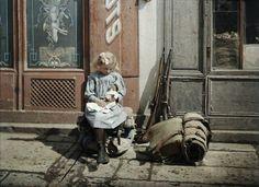 Fillette jouant à la poupée dans la rue, à côté d'elle, des fusils et un sac de soldat, Reims (Marne) 1917, Fernand Cuville, autochrome