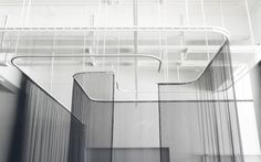 Kvadrat  Transition is an interactive installation, created by contemporary art agency AVPD, which explores the perception of space. It consists of four thin, translucent black Trevira CS curtains suspended from the ceiling, which move back and forth on curved runners, creating dynamic dividers: