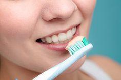 Avec une brosse à dents au grattoir intégré