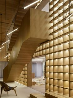 A solid timber staircase is suspended from one side of a huge double-storey bookcase inside this sales office located on the outskirts of Shanghai.