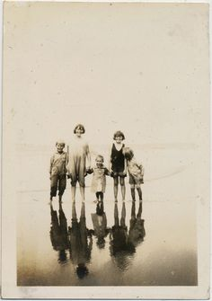 Five children standing together on the seashore. Their reflections can clearly be seen before them in the calm watery sand. - 不寛容の楽園/孤児