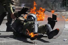 A riot police officer reacts after he was hit by a petrol bomb thrown by protesters during a nationwide general strike in Athens. Nearly 34,000 people marched in Athens and another 18,000 in Thessaloniki in the first general strike to be held since the new government took office in June.