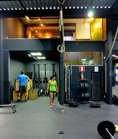 Academia CrossFit BH 3 - Área de treino em piso emborrachado preto. Telha sanduíche, estrutura e instalações aparentes em estilo industrial. Paredes pintadas de preto.