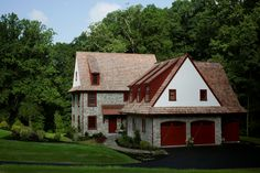 Custom period style home with red accents, stone veneer, dormers, and a 3-car garage.