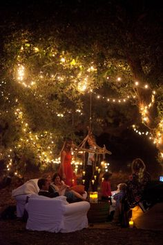 Backyard party with fairy lights. I love how they just moved indoor furniture outside