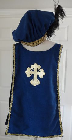 New childs Renaissance Medieval Tudor knight tunic with hat robe 3 musketeer costume. This blue professional quality plush tunic with matching floppy hat is fully lined with gold trim on tabard edging and hatband. Ostrich feather to complete the regal hat. Tabard is embellished with a