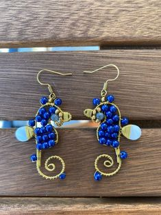 Delicate earrings made with beads and brass wiring to create a seahorse earring. All of these are handmade in Thailand. Color options include: Purple, blue, green, and red.