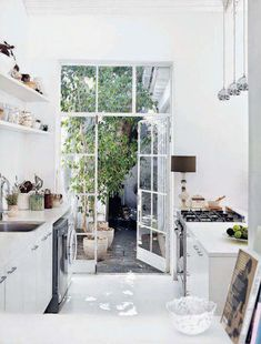 bright white kitchen with french doors leading to a lovely courtyard.