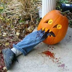 Scary Halloween Pumpkin Carvings | scary-pumpkin-carvings // use a pool noodle, an old cut up pair of jeans, a sock, and an old sneaker to create the leg