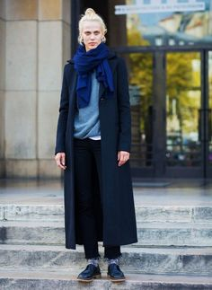 Aymeline Valade wears a gray sweater, long coat, navy blue scarf, frayed-hem jeans, and oxfords