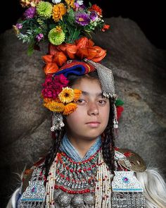 Drokpa woman from the Dah valley in the Himalaya with her beautiful traditional dress decorated with flowers and jewelry by peter@subexposure.com