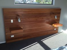 Decking headboard with floating shelves and dangling lights..
