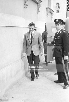 American jazz trumpet player and singer Chet Baker being sued for possession. He's escorted by a carabiniere toward the Court house. Lucca 1962