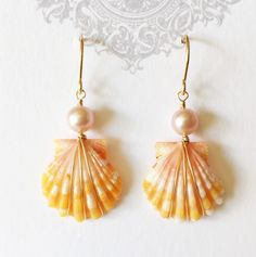Vibrant orange color sunrise shells beautifully hand wrapped with 14k gold filled wire and pink fresh water pearls suspended from 14k gold filled handmade French ear wires. Sunrise shell are about nic