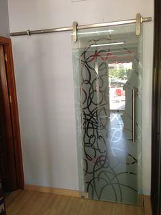 Puerta corredera de vidrio templado decorado con sistema de acero inoxidable.