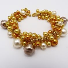 Gold Glass Pearl Cluster Bracelet.  Jingly jangly cluster bracelet with lots of cold, cream and bronze coloured glass pearls on gold plated wrapped headpins, with a gold plated heart clasp. Price: £12.00 inc postage.  See www.tiggyboojewellery.co.uk for more