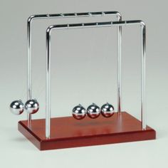 """Newton's Cradle 7.0""""   Be amazed as only the first and last sphere move  • Solid metal and wood construction  • Popular as an executive desktop toy"""