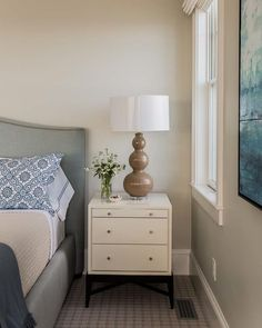 Next to the bed in the master bedroom is achalwhite glass cabinet with polished nickel pulls from Icon Group and a fluted clay gourd lamp in a muted ginger color. The room'scalm tones create a relaxing and soothing look in this summer home.