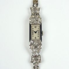 Platinum diamond cocktail watch. Platinum diamond cocktail watch. The old cut diamond set rectangular case in the Art Deco style with cream dial, blued hour and minute hands, Arabic numerals and scrollwork engraving to the sides, to old cut diamond set links of foliate design and a 9 ct white gold bracelet with adjustable folding clasp. Manual wind movement. Total estimated diamond weight 1.28 cts. Case measures 12 mm x 25 mm. Weight 19.7 grams. Boxed. Currently in working order, however…