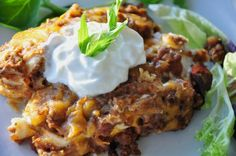 Creamy Burrito Casserole--  a layered casserole made with ground meat, onion, taco seasoning, cream soup, refried beans, sour cream, cheese, and flour tortillas.