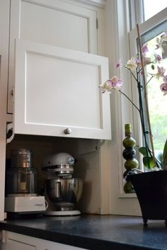 Hide those small appliances!  kitchen storage | kitchen ideas | white cabinets | black counters | interior design