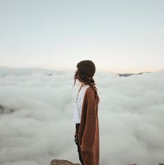 Girl in the morning above the clouds. Burnt orange cardigan, black beanie, white shirt, and braided brunette hair