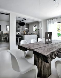 Kitchen open to the dining room and its large wooden table made in Thailand