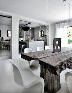 Une cuisine ouverte sur la salle à manger et son imposante table en bois de Thaïlande