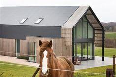 De houten lamellen en het leien dak passen harmonieus in de landelijke omgeving.