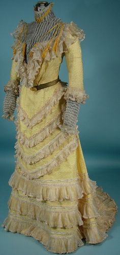 c. 1900 Victorian Yellow Silk Jacquard 2-piece Trained Gown with Tons of Frills! The 2-piece gown is made of yellow silk jacquard built on a cotton lining, the ruffles are a fine netting, the bodice and cuffs have an inner lining of gold lame.  The belt is also gold lame.  The ornamental buckles may be newer. Yellow velvet thin ribbons highlight the bodice. The only other thing to mention is that the ruffles are applied on a white braid and then sewn onto the gown I AntiqueDress.com
