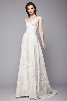 Off White A-line gown in embroidered Tulle with plunging neckline and wrap bust made of ribbon bands.