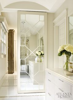 Beautiful bathroom with barreled ceilings and light tan walls which highlight a geometric mirrored closet door over large scale white tiled floors accented with mosaic trim.