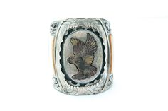 "MEN'S EAGLE INLAID SILVER CUFF BY J. QUAM (MID 20TH CENTURY). Signed ""J Quam"". Zuni bracelet with inlaid tiger's eye eagle and handtooled leaf motif . Vertical insets of mother-of-pearl, abalone, coral and turquoise. 3.25""h. 2.75""w. Estimate $ 800-1,400 garths.com"