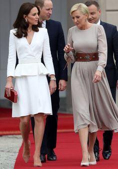 17 de julho de 2017 - Catherine desembarcou em Varsóvia para uma viagem de cinco dias pela Polônia e pela Alemanha ao lado de William, George e Charlotte. Elegante, Kate selecionou um vestido peplum da grife Alexander McQueen para o primeiro compromisso do dia. A clutch vermelha combinava com as joias de rubis.