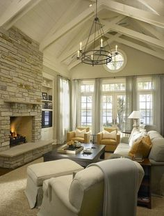 Traditional yellow & gray living room with vaulted ceiling, stone fireplace flanked by built-ins, TV, jute rug, pair of mustard yellow chairs, light gray linen slipcover sofa, blue throw, espresso chunky cocktail table, wall of French doors & transom windows and iron chandelier. Designer: Hickman Design Associates @ Home Improvement Ideas