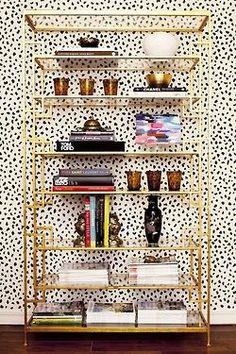 gold shelving with polka dot wallpaper