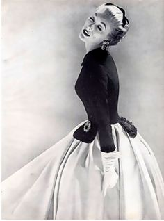 Mainbocher's elegant mid-calf skirt is of white satin topped by black taffeta jacket braided on the cuffs and the tabs. Photo by Richard Avedon, 1951.