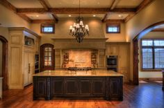 Gabriel Builders - The central feature in is the massive limestone hood mantle, weighing in excess of 700 pounds, and the 12' tall ceilings featuring hand hewn beams. The pantry is immediately behind the limestone mantle and is the size of most Kitchens. The pantry has very ornate cabinety with much storage and additional appliances and built in coffee station.