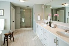 Spa like bathroom features one single vanity, divided into his and hers sections, paired with a white quartz countertop and a mosaic tiled backsplash under a full length white framed mirror lined with Boston Functional Library Wall Lights.