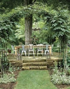 a dining area on raised block under large tree in garden - gorgeous!