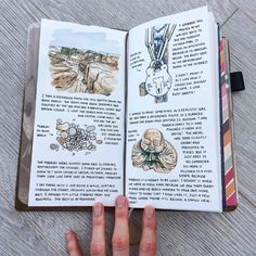 Midori travelers notebook with watercolour illustrations of some pebbles, a lock and a buddha ornament. Art journal by Clare Willcocks