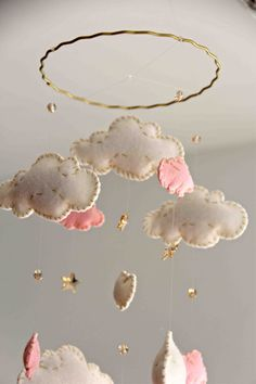 The clouds in this mobile are die cut from a wool blend felt in shades of pink and white. Each cloud is are hand stitched with gold thread.
