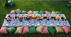 For a Moroccan-style birthday dinner, bright cushions serve as seating at a low table covered in flowers. Colin Cowie Design