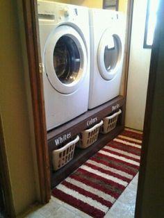 Wasmachine en droger op hoogte met wasmanden eronder.