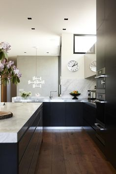 Moody black cabinetry makes a bold statement in this kitchen by Chelsea Hing