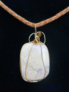 Stunning stone necklace with tan undertones wire wrapped enhanced with beads on handmade Kumihimo cord. $30.00. Please check out my website www.miselaynesjewels.weebly.com for this or more of my pieces.