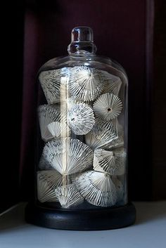 Repurpose book pages to fill a jar.  This looks like fans or shells.