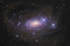 """Essa belíssima galáxia em espiral chamada Messier 63 está a 25 milhões de anos luz de distância de nós, na constelação de Canes Venaciti (conhecida por aqui como """"Os Cães de Caça).  Catalogada como NGC 5055, ela tem 100 mil anos luz de comprimento – a"""